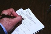 Hand completing a form